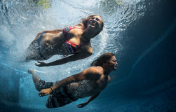 Couple in the pool. Underwater shot of the couple jumping in the pool Stock Images