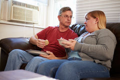 Couple With Poor Diet Sitting On Sofa Eating Meal Royalty Free Stock Photo