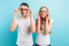 Couple with poor eyesight a man and a woman with glasses are looking into the camera trying to see something, on a blue background. Young couple with poor royalty free stock image