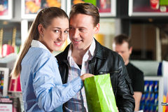 Couple with popcorn in cinema lobby Royalty Free Stock Images