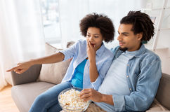 Couple with popcorn watching tv at home Stock Image