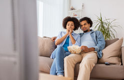 Couple with popcorn watching tv at home Stock Photography