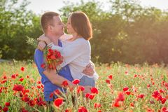Couple among poppy field embracing and smiling royalty free stock images