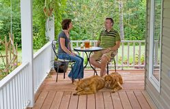 Couple on Porch. A couple with their dogs enjoying a glass of ice tea on their porch Stock Image