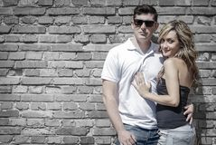 Couple portrait in front of brick wall royalty free stock photography