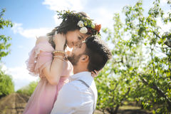 Couple portrait of a girl and guy looking for a wedding dress, a pink dress flying with a wreath of flowers on her head on a backg Royalty Free Stock Photography