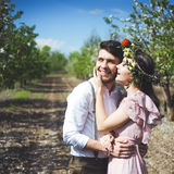 Couple portrait of a girl and guy looking for a wedding dress, a pink dress flying with a wreath of flowers on her head on a backg Stock Photography