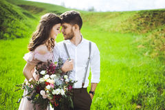 Couple portrait of a girl and guy looking for a wedding dress, a pink dress flying with a wreath of flowers on her head on a backg Stock Photos