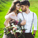 Couple portrait of a girl and guy looking for a wedding dress, a pink dress flying with a wreath of flowers on her head on a backg Royalty Free Stock Photo