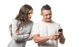 couple portrait Man som ser till hans telefon Den ilskna upprivna kvinnan som rymmer armar korsade och, ser över hans skuldra på  royaltyfria foton
