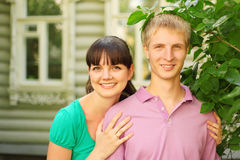 Couple pose near wooden village house Stock Photo