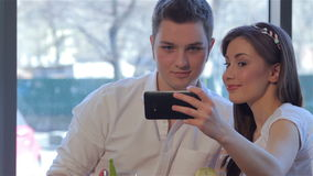 Couple poses to a selfie at the cafe. Attractive young couple posing to selfie at the cafe. Handsome caucasian man hugging his girlfriend in front of phone stock video