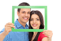 Couple posing behind a green picture frame Stock Images