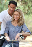 Couple posing by bicycle. Couple taking abreak during bike ride Stock Photos