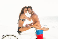 Couple posing with bike on the beach Stock Photo