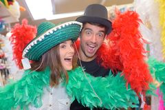 Couple posing in fancy dress hats and boas. Feather stock image