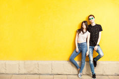 Couple posing in fashion style on yellow wall Royalty Free Stock Photos