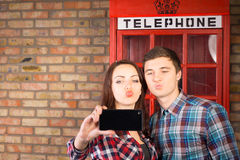Couple posing in front of a British phone booth Stock Photos