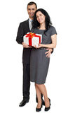 Couple posing with gift box, people dressed in classic black suit, isolated on white background Royalty Free Stock Image