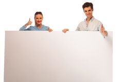 Couple posing holding a blank billboard Stock Image