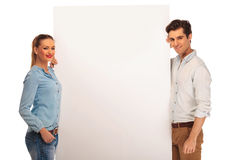 Couple posing holding a white billboard royalty free stock photography