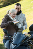 Couple posing near motor bike with sandwitches and coffee Stock Images