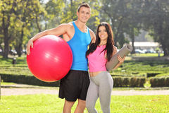 Couple posing in park with fitness equipment Royalty Free Stock Image
