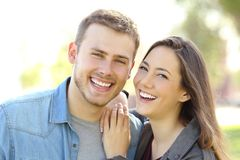 Couple posing with perfect smile and white teeth. Front view of a couple posing outdoors with perfect smile and white teeth and looking at you in a park with a stock photography