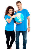 Couple posing for a picture with globe in hand. All on white background Stock Photography
