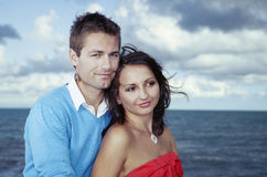 Couple posing for portrait. Young couple posing by the sea on stone baffle pier in Italian tourist resort Caorle in various dresses stock photo