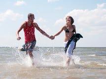 Couple posing on the sandy sea coast Royalty Free Stock Photo
