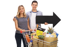 Couple posing with a shopping cart and an arrow Stock Photography