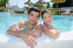 Couple posing in swimming pool Royalty Free Stock Images