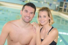 Couple posing in swimming pool area stock images