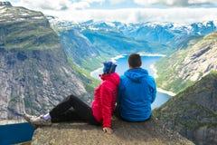Couple posing on Trolltunga Norway. Couple posing on Trolltunga. Happy women and men enjoy beautiful lake and good weather in Norway stock images