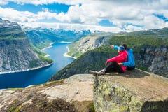 Couple posing on Trolltunga Norway. Couple posing on Trolltunga. Happy women and men enjoy beautiful lake and good weather in Norway Royalty Free Stock Photography