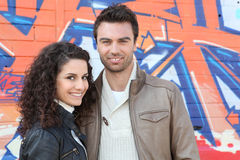 Couple posing by wall Royalty Free Stock Photo