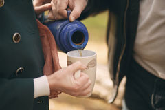 Couple pours tea from a thermos into the cup to warm up on the s Stock Image