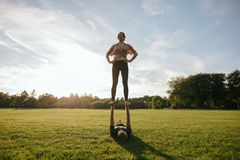 Couple practicing acrobatic yoga in park Stock Image