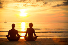 Couple practicing  on the beach at sunset. Royalty Free Stock Image