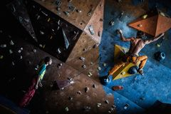 Couple practicing rock-climbing on a rock wall Stock Photos