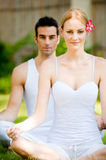 Couple Practicing Yoga. An attractive caucasian couple practicing yoga outdoors stock photo