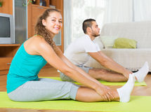 Couple practicing yoga at home Stock Photos