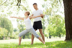 Couple practicing yoga in the park Royalty Free Stock Photo