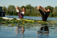 Couple practicing yoga on the river Royalty Free Stock Photos