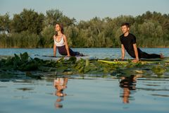 Couple practicing yoga on the river Stock Image