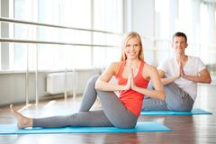 Couple practicing yoga. Young couple doing yoga exercises in fitness club Royalty Free Stock Photography