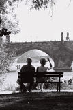 Couple in Prague. Couple sitting in a bench, watching the river in Prague Stock Photos