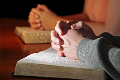 Couple Praying Bibles. A man and woman pray together with their hands resting upon Holy Bibles (Christian Image, shallow focus point on man's hands stock image