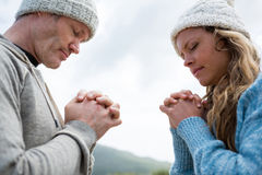 Couple praying with hands clasped. On beach Stock Photos